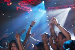 Enthusiastic crowd with arms raised on dance floor of nightclub - stock photo