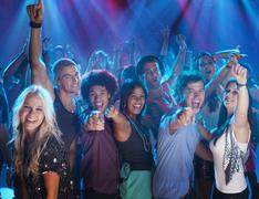 Portrait of enthusiastic crowd on dance floor of nightclub - stock photo