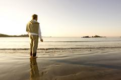 A man pauses while skipping rocks into the water at Bailey's Beach on an autumn Stock Photos