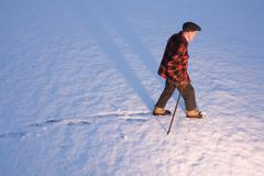 An elderly man walking in the snow using a cane, New England, USA - stock photo