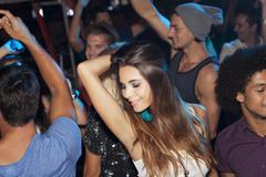 Confident woman dancing in crowd at nightclub - stock photo