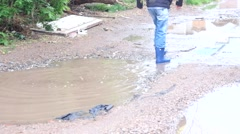 Happy child playing in puddle after the rain Stock Footage