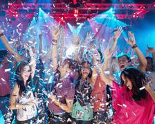 Confetti falling over enthusiastic crowd on dance floor of nightclub - stock photo