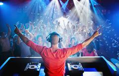 DJ with arms outstretched overlooking dance floor Stock Photos