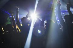 Spotlight over crowd dancing on dance floor - stock photo