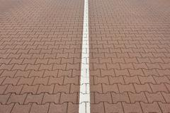 Close-up of road with interlocking brick stones and white line, Norderney, East - stock photo