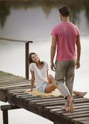 Woman smiling at approaching man on dock over lake Stock Photos