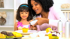 lifestyle recreation African American mother female child kitchen icing cupcakes - stock footage