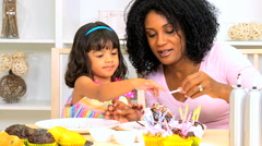 Ethnic African American female child mother organic cupcakes icing togetherness Stock Footage