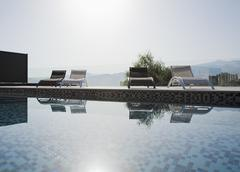 Sun shining over lounge chairs and swimming pool Stock Photos