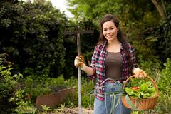 young woman in the garden holding a basket of fresh vegetables and a rake - stock photo