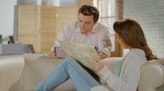 Happy just married couple planning honeymoon trip, checking map Stock Footage