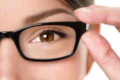 Glasses eyewear closeup - f woman holding eye glasses frame smiling Stock Photos