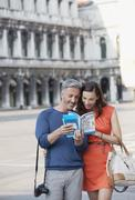 Smiling couple looking at guidebook in St. Mark's Square in Venice - stock photo