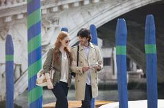 Smiling couple with guidebook walking in Venice - stock photo