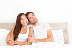 Happy couple in bed thinking and dreaming together looking up - stock photo