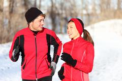 Couple running in winter snow living healthy lifestyle Stock Photos