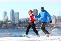 Winter couple fun on snowshoe in Montreal Stock Photos