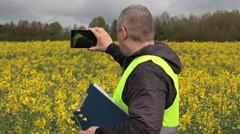 Farmer filmed with tablet PC yellow rape field - stock footage