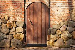 Wooden door in a stone fence Stock Photos