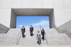 Business people descending urban stairs Stock Photos