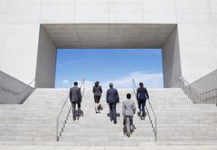 Business people ascending modern stairs Stock Photos