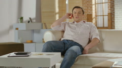 Young man sitting on sofa at home, having phone conversation - stock footage