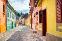 Sighisoara, Romania - June 23, 2013: Stone paved old streets with colored hou Stock Photos
