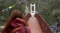 Woman walking over bridge with buddhist prayer flags, long shot, shallow DOF Stock Footage