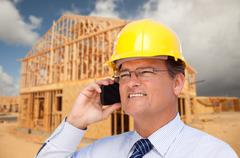 Contractor in Hardhat at Construction Site Talks on His Cell Phone. Stock Photos
