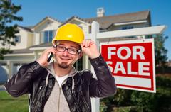 Contractor in Hard Hat in Front of House and For Sale Real Estate Sign. Stock Photos