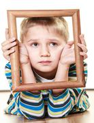 Little sad boy child framing his face - stock photo