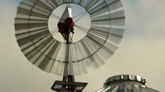 Windmill Spins Fast Above Farm Silo Pumping Water - stock footage