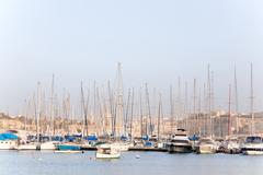 Early winter morning at Marsamxett harbour. Many sailing yachts lie alongside Stock Photos