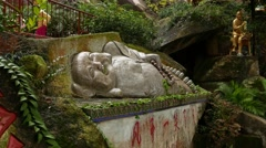 Stony lying Buddha sculpture in foresty hillside, golden statues on slope Stock Footage