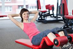 Smiling woman workout with training machine in the gym Kuvituskuvat
