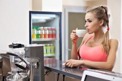 Sportive woman with cup in the gym bar Stock Photos
