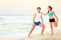 Couple doing stretching exercises workout training on beach Kuvituskuvat