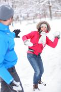 Young couple playing in the snow having fun snowball fight together in winter Kuvituskuvat