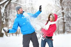 Young couple having fun snowball fight together in snow in winter Kuvituskuvat