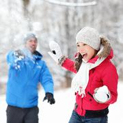 Winter fun - couple in snowball fight  having fun together in forest snow Kuvituskuvat