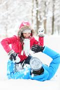 Winter couple snowball fight -  Young couple having fun in snow outside Kuvituskuvat