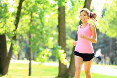 Runner - woman running in park Asian / Caucasian fitness sports model - stock photo