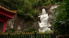 White statue of Kuan Yin standing on Dragon, against rocky waterfall Stock Footage