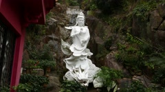 White statue of Kuan Yin riding Dragon, against rocky wall background Stock Footage