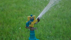 Macro of head of garden sprinkler working slowmo Stock Footage