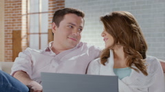 Beautiful wife and husband cuddling up on couch, shopping online Stock Footage