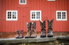 Cowboy boots in front of a red barn. - stock photo