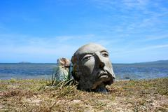 Abstract. Stone human head in the sand. - stock photo