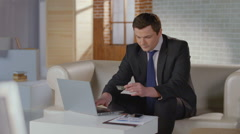 Rich man business suit inserting credit card number on laptop Stock Footage
